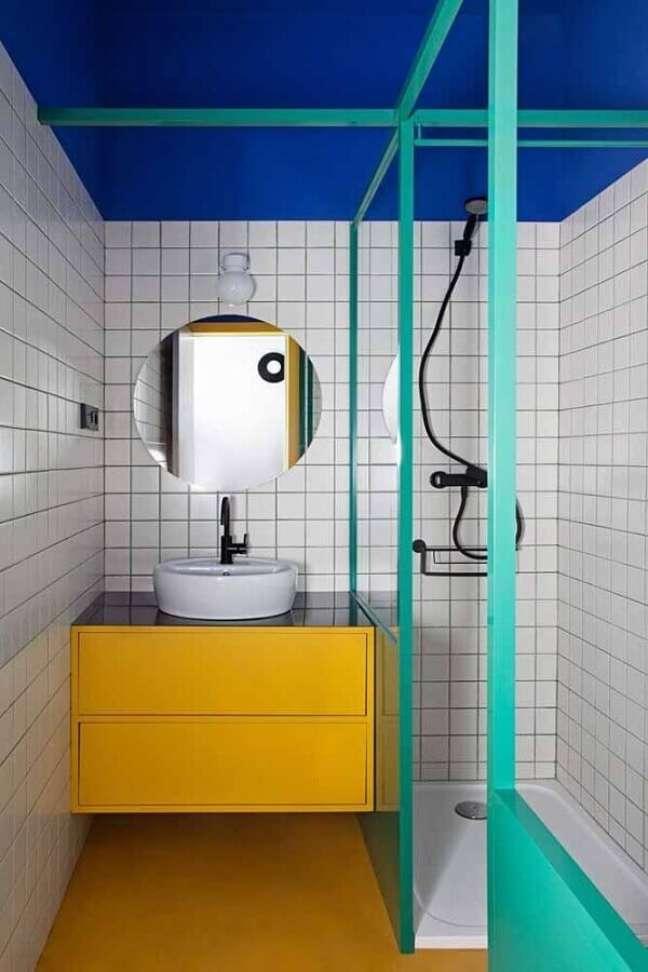 6. Box cor ciano para banheiro pequeno decorado com teto azul e gabinete amarelo – Foto: Architectural Digest