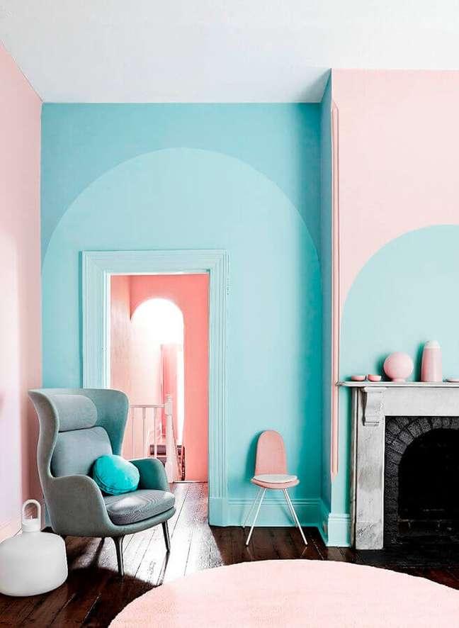 5. Sala com lareira decorada com parede cor ciano e detalhes em cor de rosa – Foto: Behance