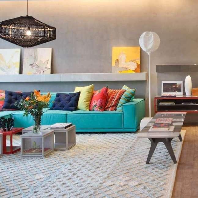 12. Almofadas coloridas para sofá cor ciano em sala moderna decorada com parede de cimento queimado – Foto: Paula Neder Arquitetura