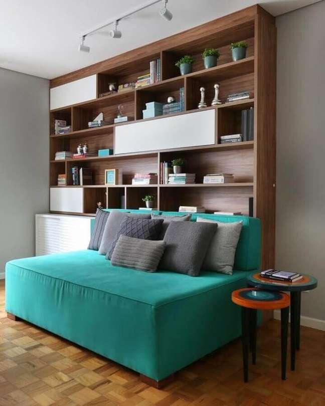61. Sofá sem braço cor ciano para decoração de sala com estante de madeira – Foto: GF Projetos