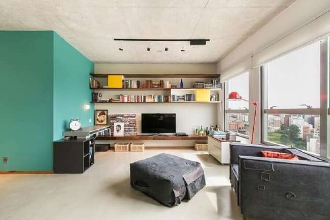 23. Cor de tinta azul ciano para parede de sala decorada com prateleiras de madeira – Foto: DT Estúdio Arquitetura