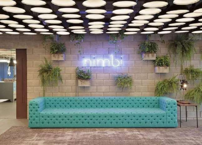 1. Decoração com vasos de plantas na parede e sofá cor ciano capitonê – Foto: Melina Romano Interiores