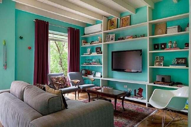 8. Parede cor ciano para sala de TV decorada com sofá cinza – Foto: Julia Ribeiro Fotografia