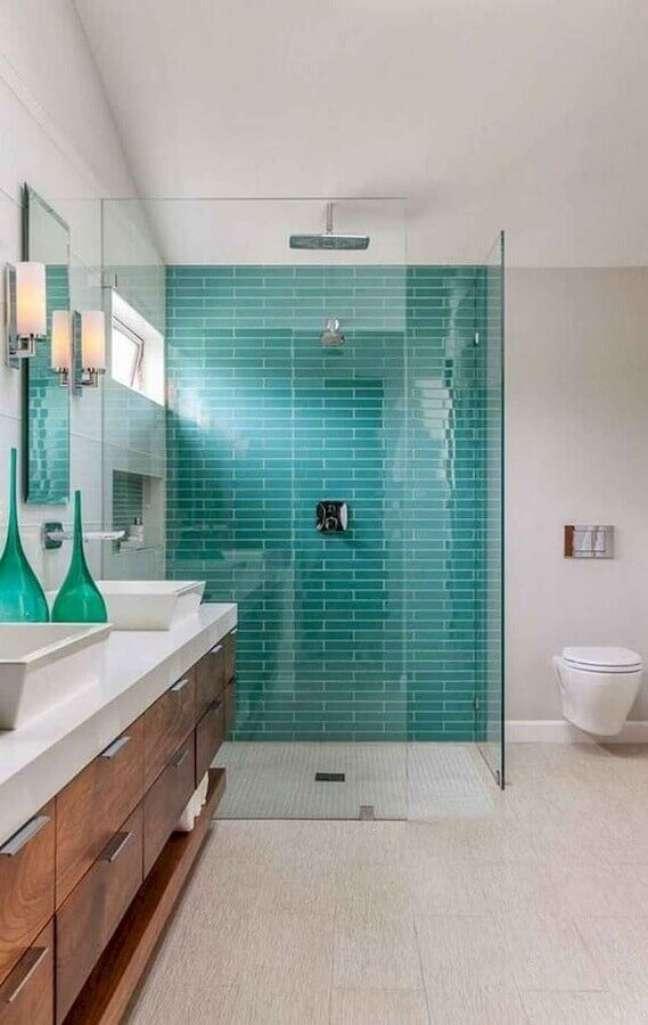 15. Banheiro grande decorado com gabinete de madeira e revestimento de parede cor ciano – Foto: The Cavender Diary