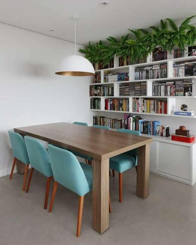 2. Cadeira cor azul ciano para decoração de sala de jantar com estante branca para livros – Foto: GF Projetos