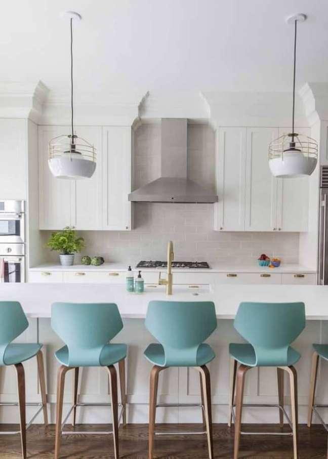 9. Cozinha com ilha branca decorada com banqueta cor ciano – Foto: Apartment Therapy