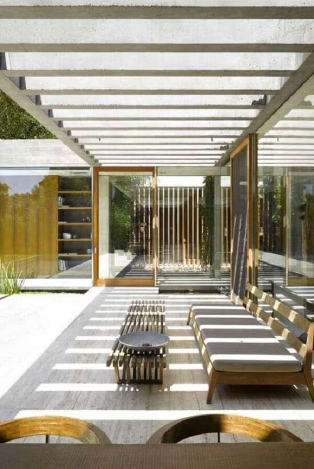 38. O pergolado de concreto com vidro traz elegância para o terraço do imóvel. Fonte: Decor Fácil