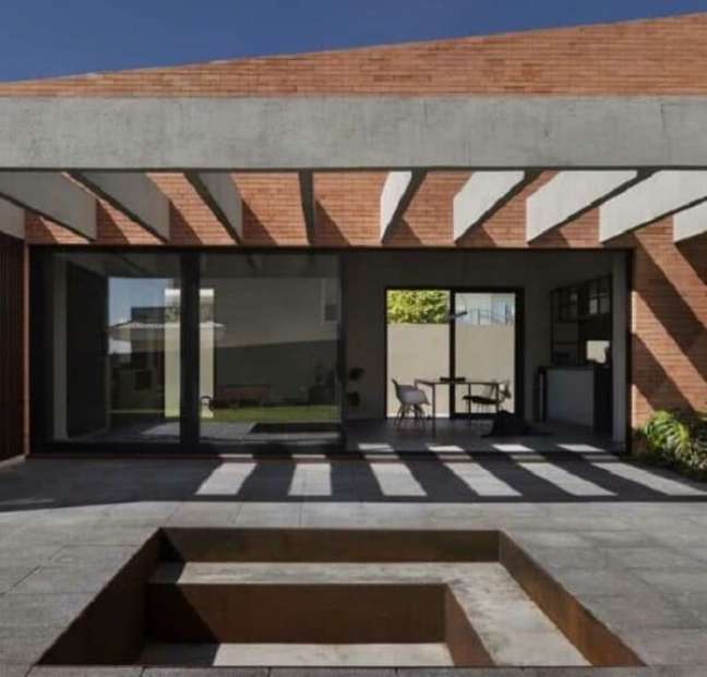 27. Fachada com pergolado de concreto na parede de tijolinho. Fonte: Decor Fácil