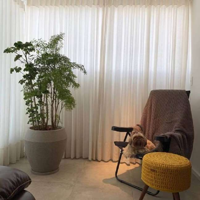 23. Decoração de sala pequena com plantas no chão e puff redondo de crochê – Foto: Verdifique
