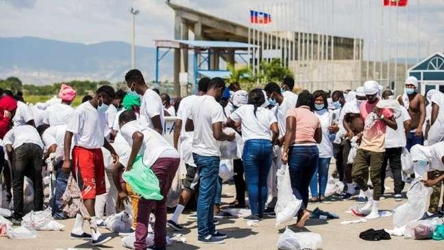 Pessoas deportadas para Porto Príncipe foram forçadas a buscar seus pertences no chão após chegarem ao Haiti