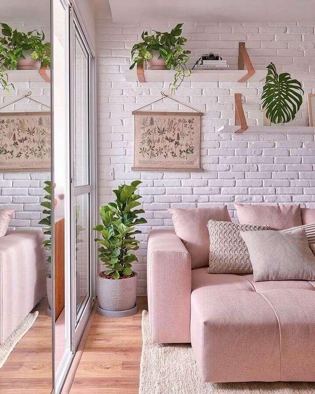 37. Sofá rosa para decoração de sala com plantas e parede tijolinho branco – Foto: Decor Fácil