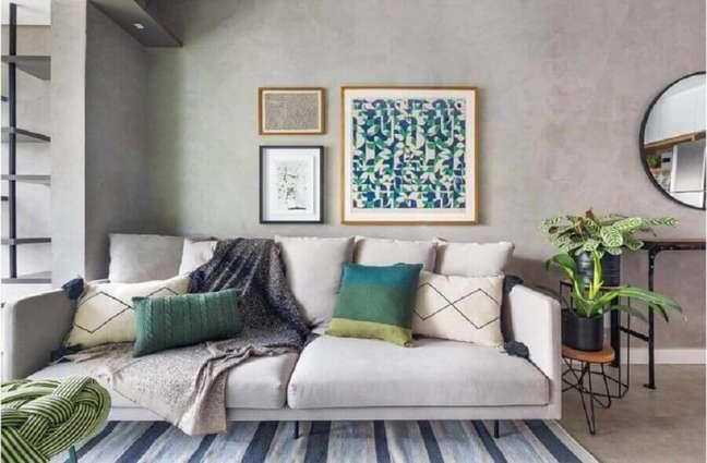 46. Vasos com plantas para decoração de sala com parede de cimento queimado e tapete listrado Foto Duda Senna