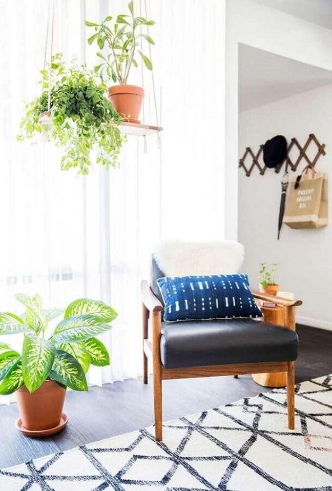 47. Vasos com plantas para decoração de sala com poltrona de couro e madeira – Foto: Decorie