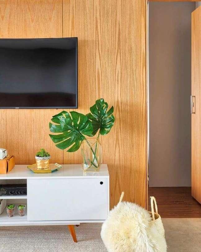 25. Painel de madeira para decoração de sala com plantas artificiais em vaso de vidro – Foto: Dudi Duarte