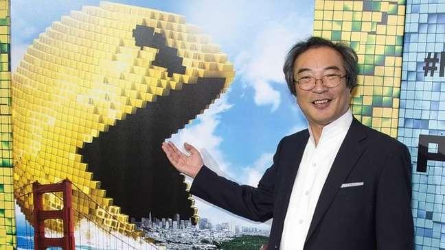 Toru Iwatani ao lado do pôster do filme Pixels