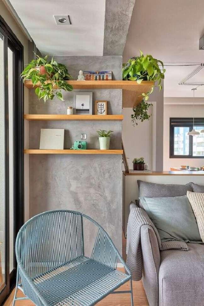 26. Parede de cimento queimado com prateleiras de madeira para decoração de sala com plantas – Foto: Voa Arquitetura