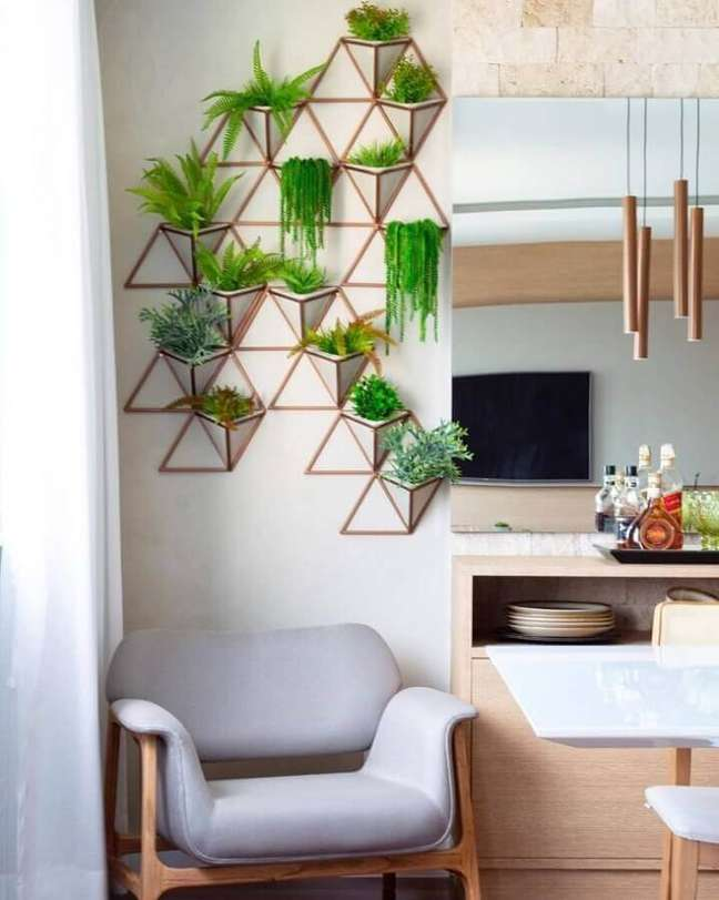 18. Decoração de sala com plantas naturais na parede e poltrona cinza – Foto: Tamiris Ribas Arquitetura