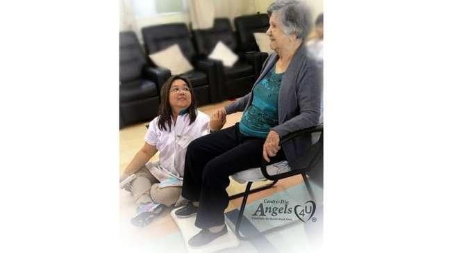 Nakamura ajudando uma idosa no centro-dia a se divertir com games