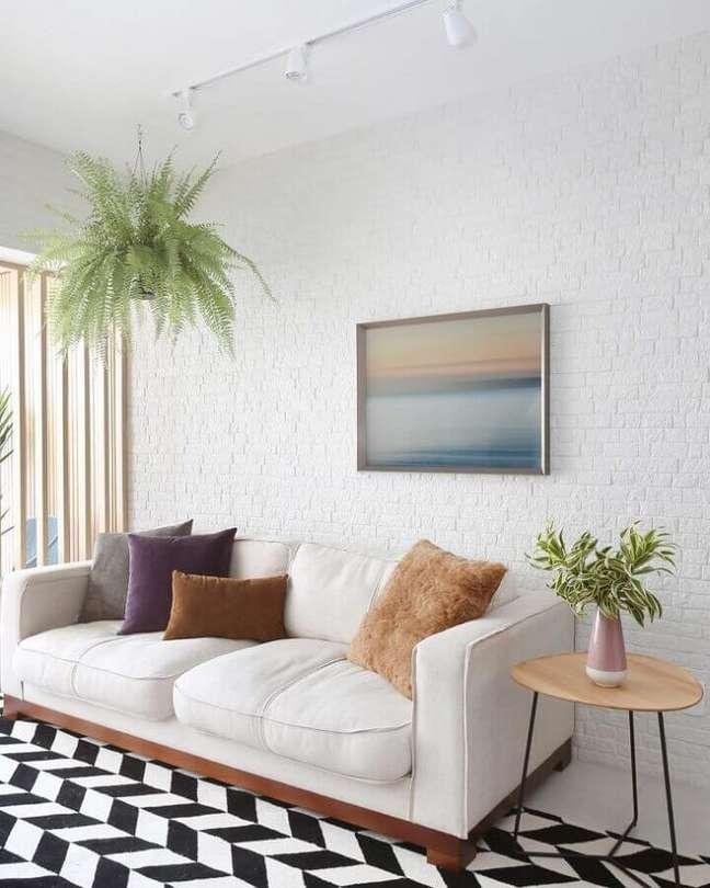 8. Cores claras para decoração de sala com plantas naturais e tapete preto e branco – Foto: Bianchi e Lima Arquitetura