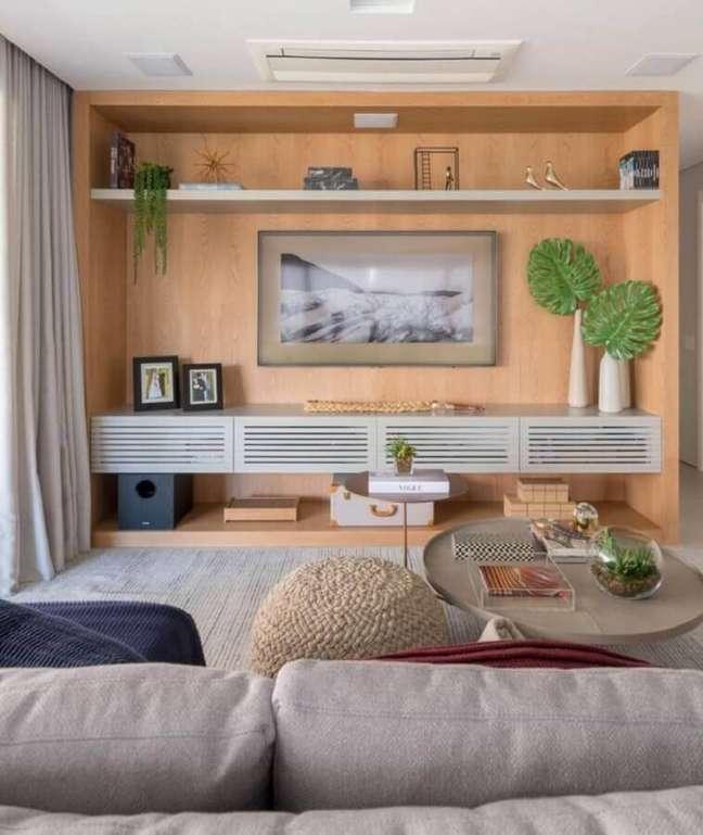 57. Vasos com plantas para decoração de sala em cores neuras com estante planejada de madeira – Foto: Dudi Duarte