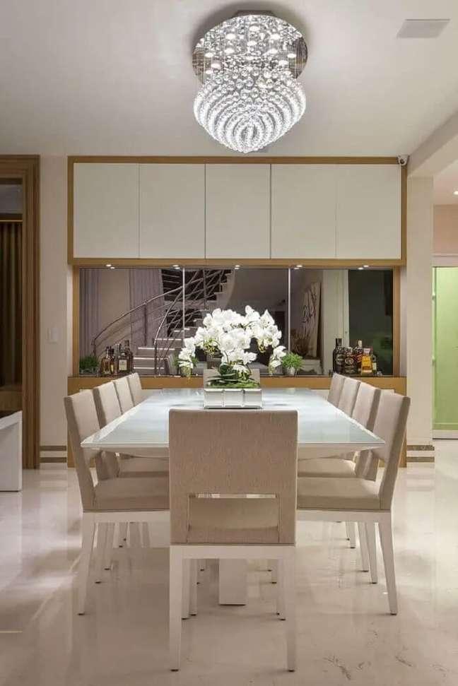 7. Modelo diferente de pendentes para sala de jantar de cristal toda branca com parede espelhada. Fonte: Iara Kilaris