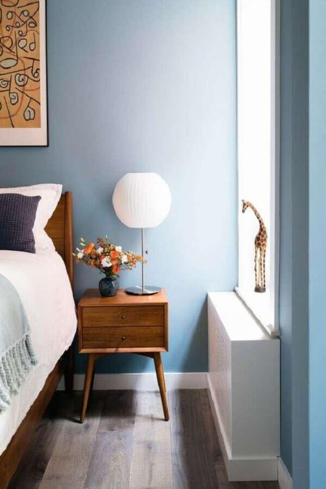 50. Quarto azul decorado com móveis de madeira e abajur para criado mudo – Foto: Amy Barkow