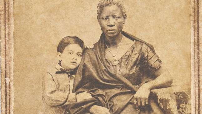 Augusto Gomes Leal com sua ama de leite Mônica, em fotografia de João Ferreira Villela, de 1860