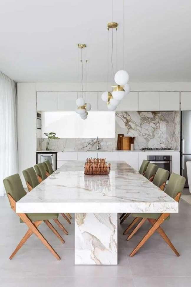 1. Cozinha americana com mesa de jantar branca feita de granito. Fonte: Leandro Garcia