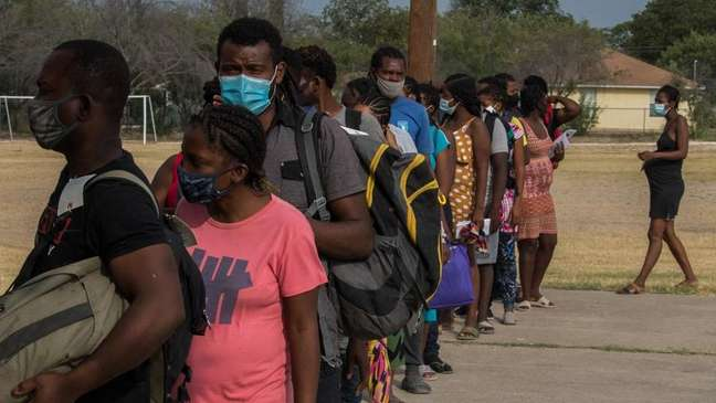 Imigrantes com o processo de asilo em andamento formam fila em um dos abrigos da região antes de seguirem para as cidades onde vão morar