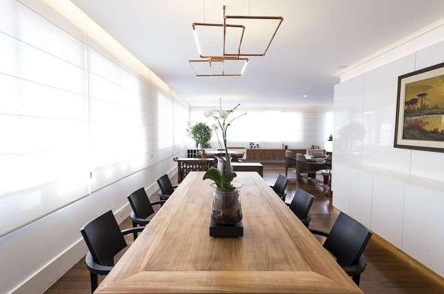 31. Sala de jantar de apartamento de luxo com mesa de madeira e cadeiras em tom preto. Fonte: Carla Cuono Arquitetura e Interiores