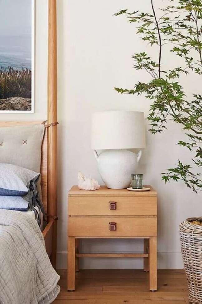 12. Abajur para criado mudo de quarto decorado com vaso de plantas e moveis de madeira – Foto: Anthropologie