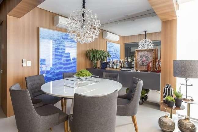 18. Cadeiras de luxo para sala de jantar em tom cinza e lustre de cristal. Fonte: Altera Arquitetura