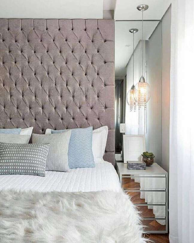 22. Modelo de cabeceira capitonê cinza para quarto com parede e criado-mudo espelhado – Foto: Mechan Arquitetura