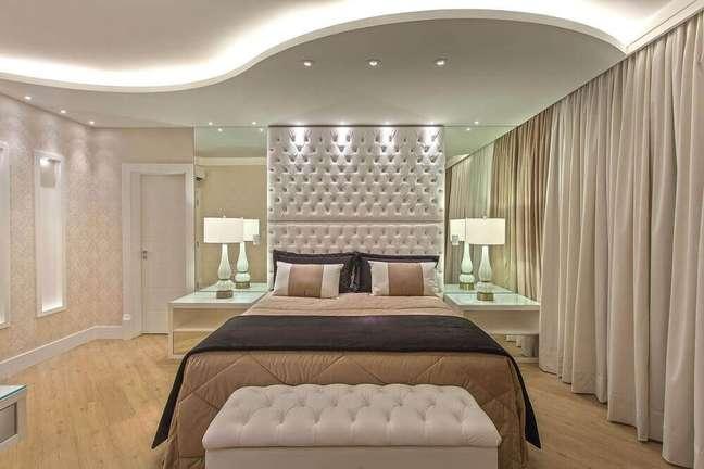 40. A cabeceira queen capitonê é perfeita para quarto com decoração sofisticada com parede espelhada – Foto: Iara Kilaris