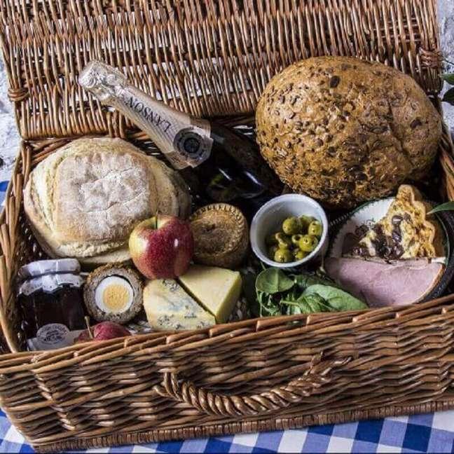 50. Uma cesta de vinhos, pães, queijos e geleias é uma excelente ideia de presente para festa na caixa – Foto: Wild Picnics