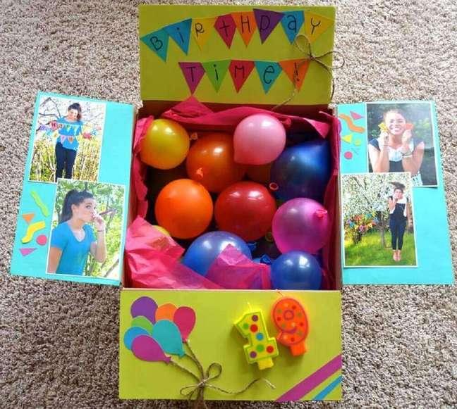 61. Ideia de festa na caixa para amiga toda decorada com balões coloridos e fotos – Foto: Hero Care Packages