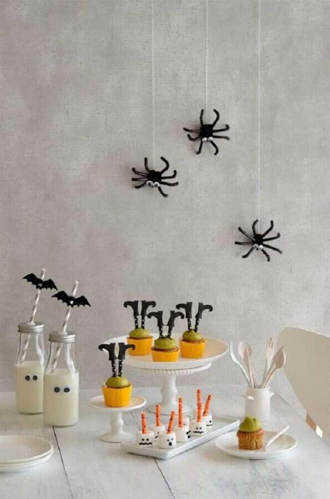 42. Parede de cimento queimado decorada com aranhas de brinquedo para festa de Halloween – Foto: Lushome