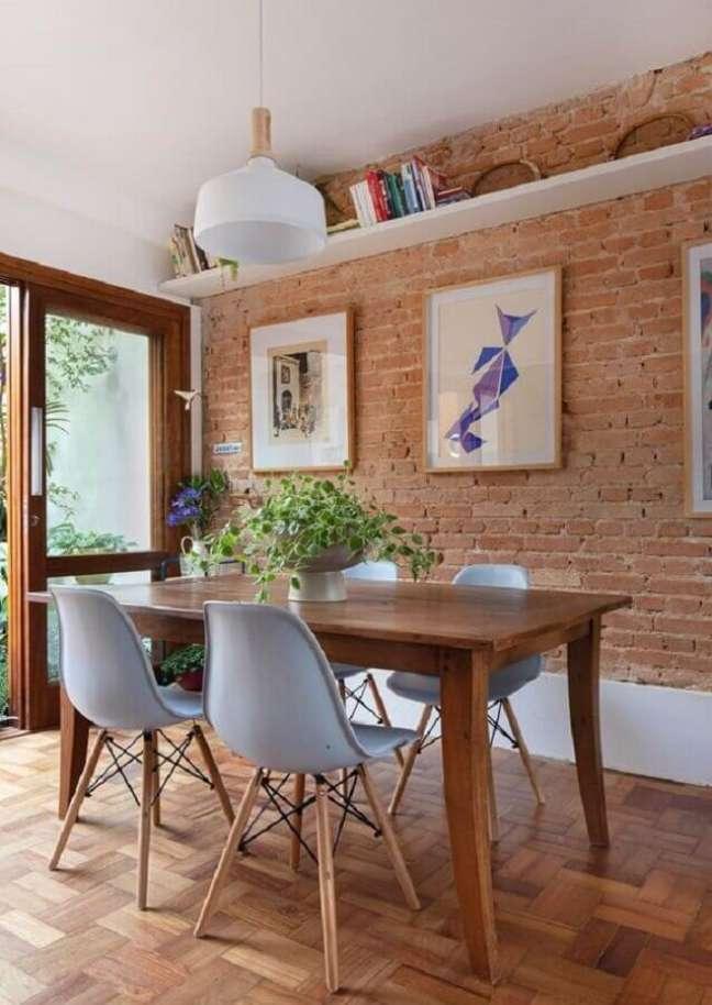 44. Quadros para sala de jantar rústica decorada com parede tijolinho e mesa de madeira – Foto: Rafaela Paoli