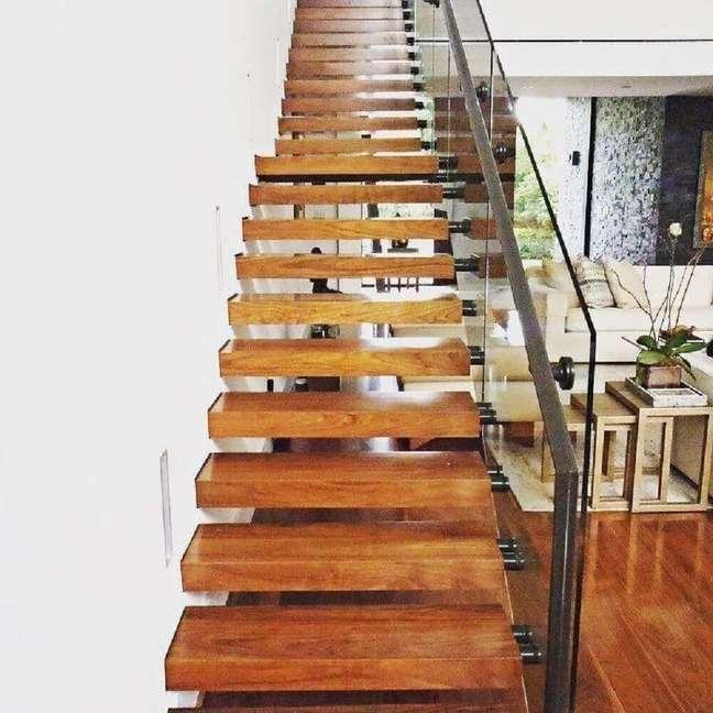 45. Escada de madeira para sala com guarda corpo de vidro e corrimão de ferro. Fonte: The Ofy