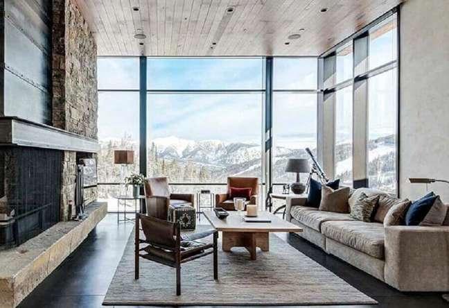 46. Revestimento de pedra para lareira de sala rústica decorada com janela do chão ao teto – Foto: Houzz