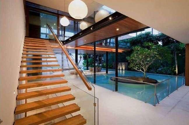 26. Escada simples de madeira com o guarda corpo de vidro. Fonte: Star Bamboo Singapore
