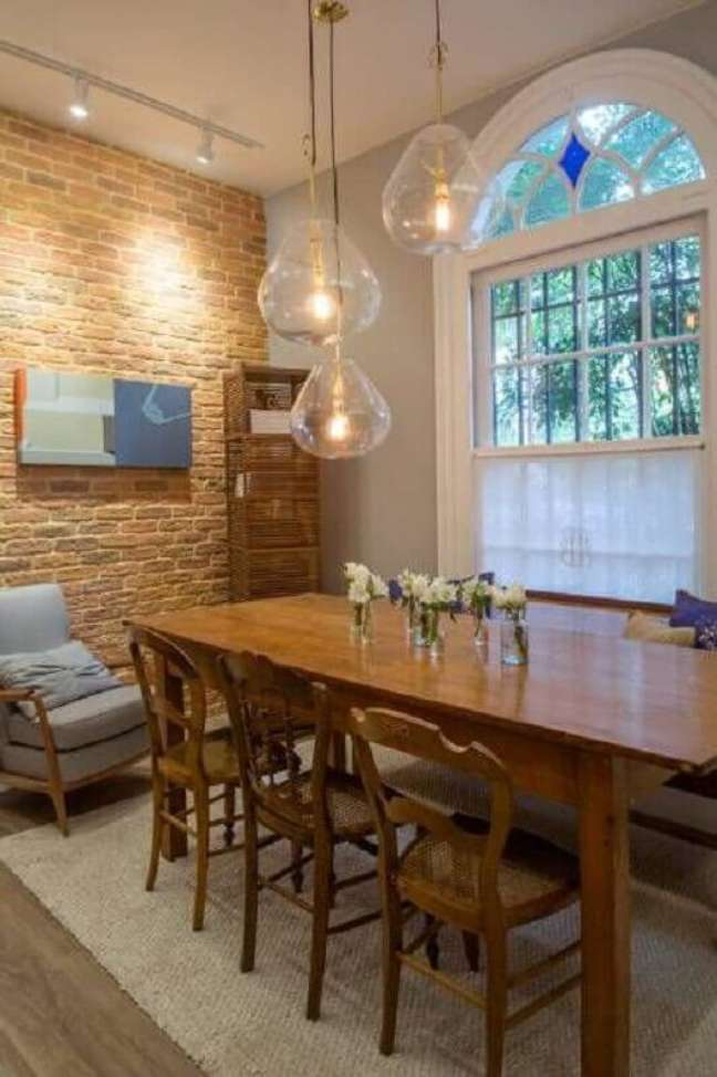 25. Decoração rústica para sala de jantar com luminária de vidro para mesa de madeira – Foto: Casacor Abril