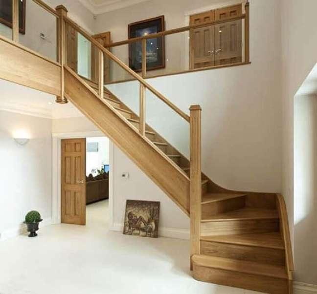 35. Escada de madeira simples com guarda corpo de vidro. Fonte: The Ofy