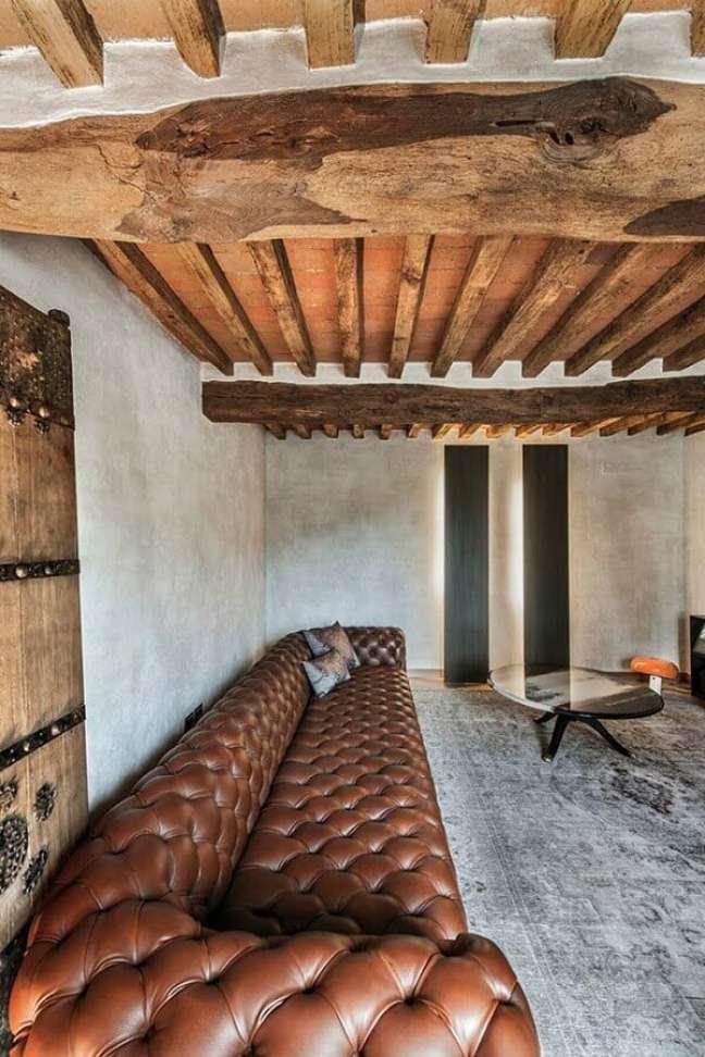 9. Sala de estar rústica decorada com sofá de couro capitonê – Foto: HomeDSGN