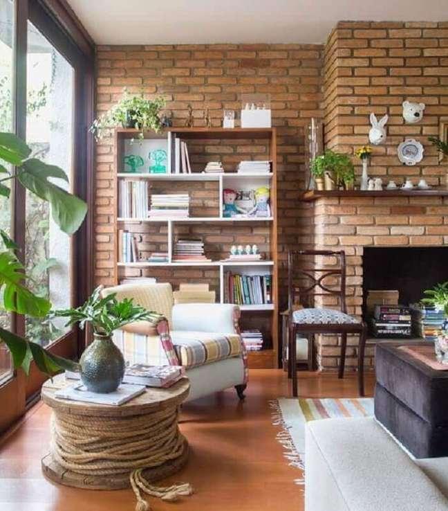 26. Estante de livros para decoração de sala rústica com lareira e parede de tijolinho – Foto: Rafaela Paoli