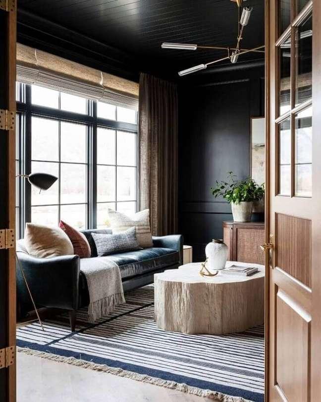 57. Sofá preto de couro para decoração de sala rústica com tapete listrado – Foto: Studio McGee