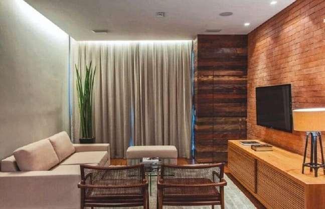 50. Sala de TV rústica decorada com parede tijolinho e poltronas de madeira – Foto: Andreoli e Fortunato Arquitetura