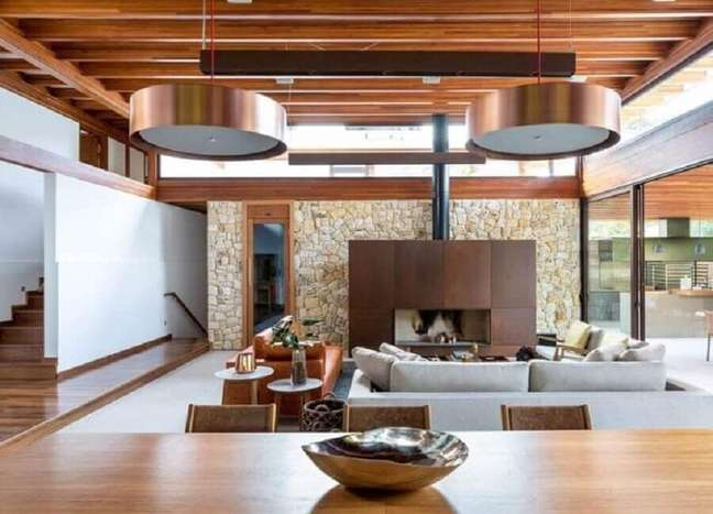 35. Parede de pedra para decoração de sala rústica e moderna com lareira – Foto: DT Estúdio