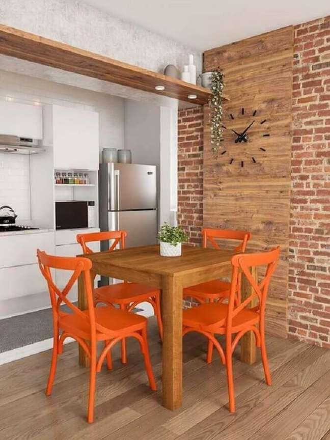 38. Parede tijolinho para sala de jantar rústica decorada com cadeira laranja – Foto: Mobly