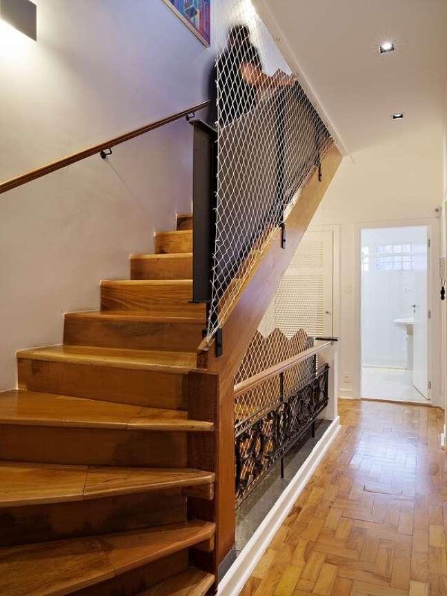 62. Além do corrimão a tela branca traz ainda mais segurança na escada de madeira. Fonte: ODVO Arquitetura e Urbanismo